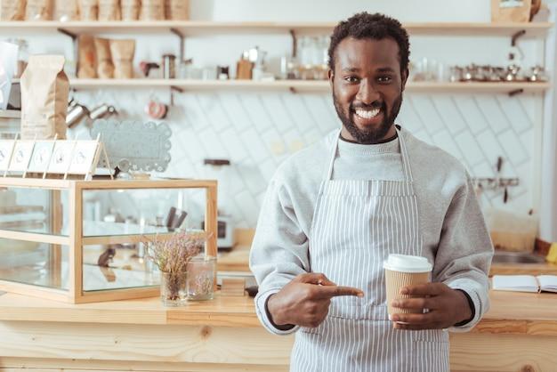 最高のコーヒー。カフェのカウンターの前に立って、カメラに笑みを浮かべながら彼の手でコーヒーのカップを指してエプロンでハンサムな若い男性のバリスタ