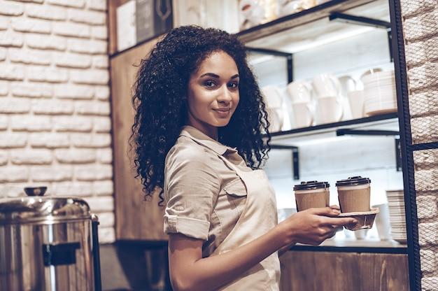 Лучший кофе в этом городе! молодая веселая африканская женщина в фартуке держит кофейные чашки и с улыбкой смотрит в камеру, стоя в кафе