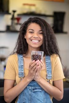 最高のコーヒー。コーヒーショップに立っているコーヒー豆のガラスと輝く白い歯の若いムラートの女性