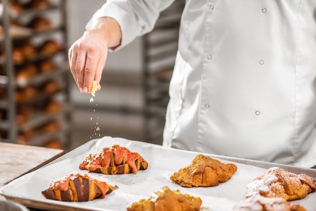 Лучшие круассаны. пекари вручную посыпают миндальными чипсами свежеиспеченный круассан, лежащий на противне в пекарне, без лица