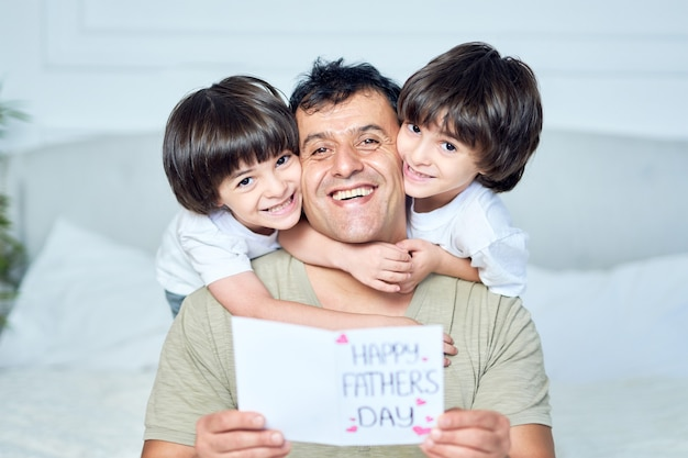 Best daddy portrait of two little latin boys brothers smiling at camera embracing their dad