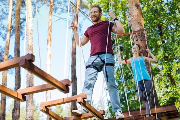 Лучшие данные. жизнерадостная молодая пара карабкается в веревочный парк, следуя друг за другом и весело улыбаясь