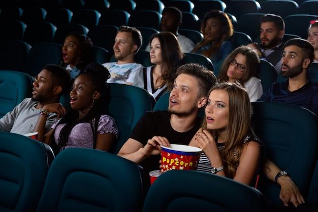 最高のデートエンターテインメント。彼らのデートの夜に映画館で映画を楽しんでいる驚いた若いカップルの肖像画