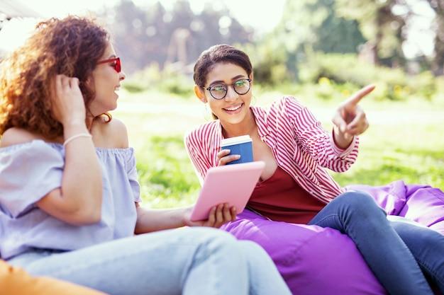 いい日。タブレットを持って友達と話している陽気な縮れ毛の女性