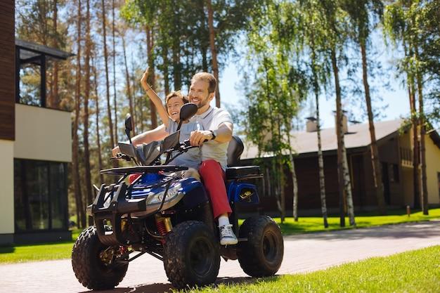 いい日。幸せな若い父は彼の息子と一緒に笑顔で全地形対応車を運転します