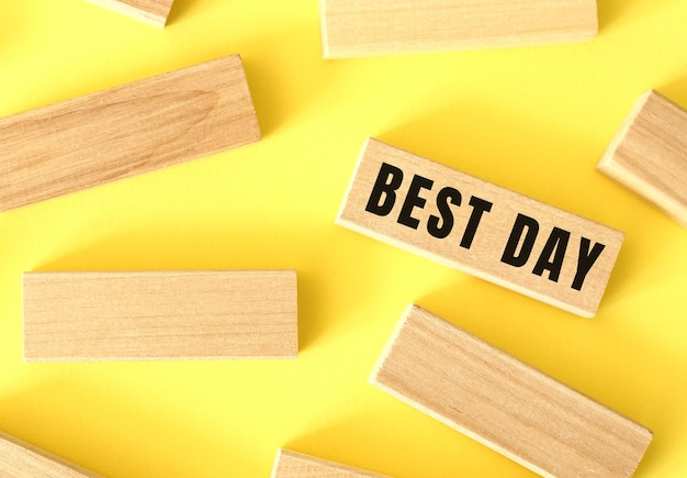 Best day text written on a wooden blocks on a yellow background