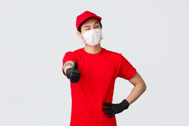최고의 배송 서비스. 의료 마스크와 장갑, 빨간 제복을 입은 열정적인 아시아 택배 직원은 최고의 배달 서비스 품질을 보장하기 위해 엄지손가락을 치켜세우고 윙크합니다.