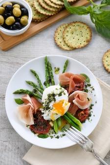 最高の卵ベネディクト-生ハム、アスパラガス、天日干しトマト、ペスト入りポーチドエッグ
