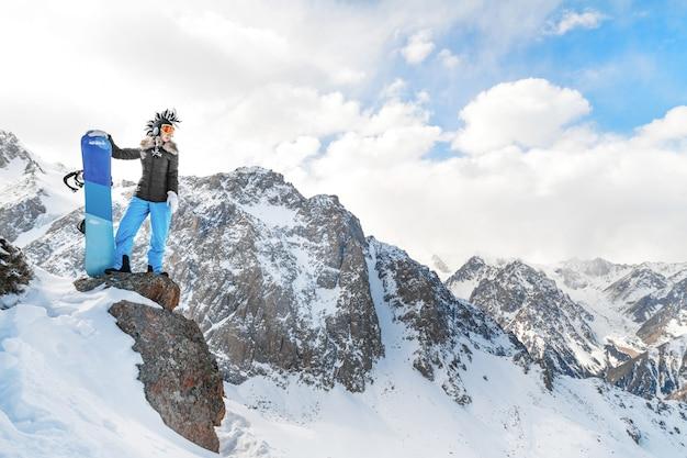 록 키 산맥에서 젊은 여성 스노 보더와 함께 최고의 서사시 익스트림 겨울 스포츠 사진. 큰 복사 공간