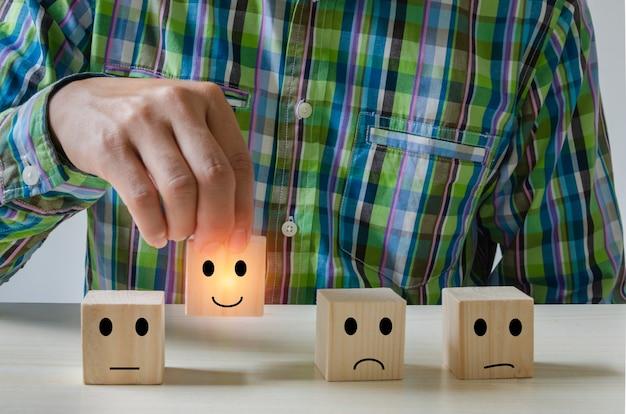 Лучший превосходный рейтинг бизнес-услуг. мужчина, держащий руку, выбирает смайлик на деревянном кубе. опрос удовлетворенности с отрицательными, нейтральными и положительными выражениями лица