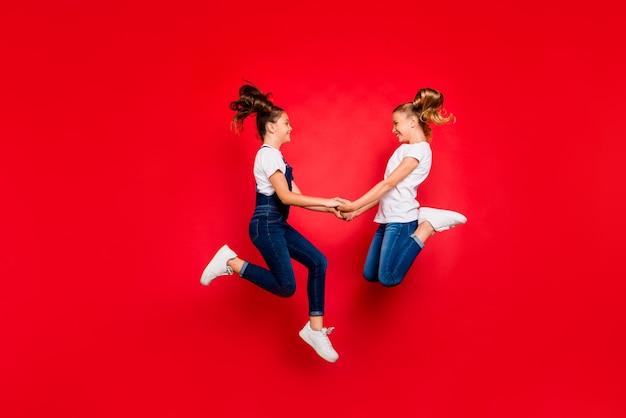 永遠に最高の仲間。 2人の面白いファンキーな子供たちのフルレングスのプロファイルサイド楽しい春の休日ジャンプは、白いtシャツデニムジーンズスニーカーオーバーオール孤立した赤い色の背景を着用してお楽しみください
