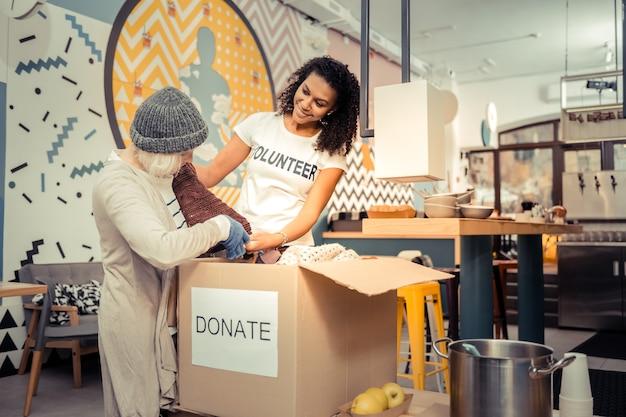 ベストフィット。高齢者の女性がいくつかの服を見つけるのを助けながら笑顔の格好良いフレンドリーな女性