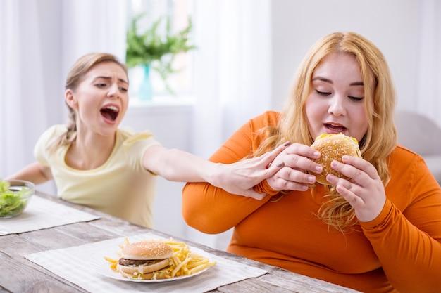 Лучшая еда. безвольная толстая женщина ест бутерброд, а ее друг останавливает ее