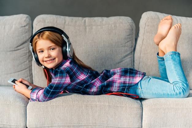Лучшее свободное время! красивая маленькая девочка в наушниках держит свой смартфон и с улыбкой смотрит в камеру, лежа на диване у себя дома