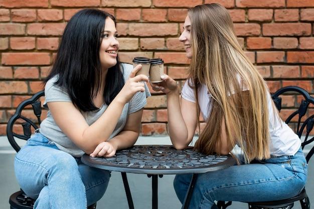 Migliori amici che esultano con bicchieri di caffè fuori
