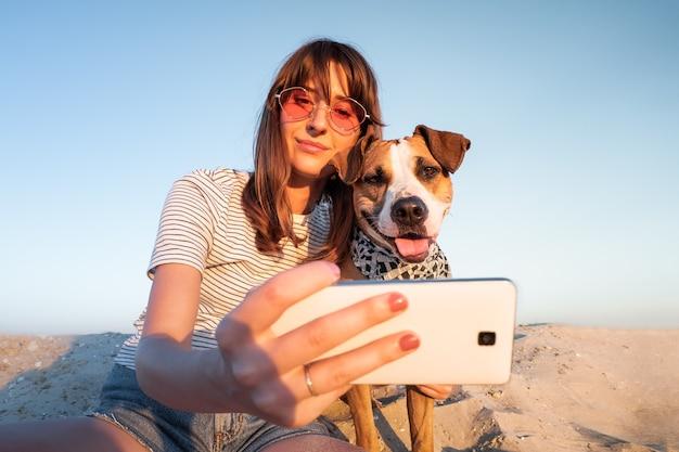 親友の概念:犬と一緒にselfieを取る人間。若い女性はビーチで彼女の子犬を屋外でセルフポートレート