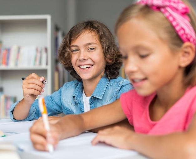 Лучшие друзья вместе делают домашнее задание в библиотеке