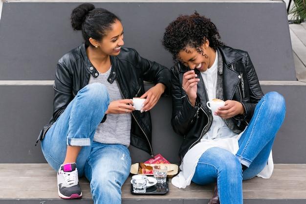Best friends drinking coffee in city