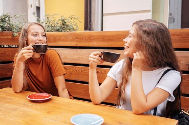 Migliori amici che bevono caffè insieme all'aperto