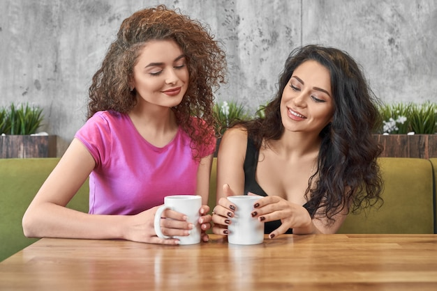 Best friends drinking tea, talking and enjoying time in cafe