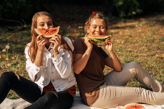 Best friends eating watermelon outdoors