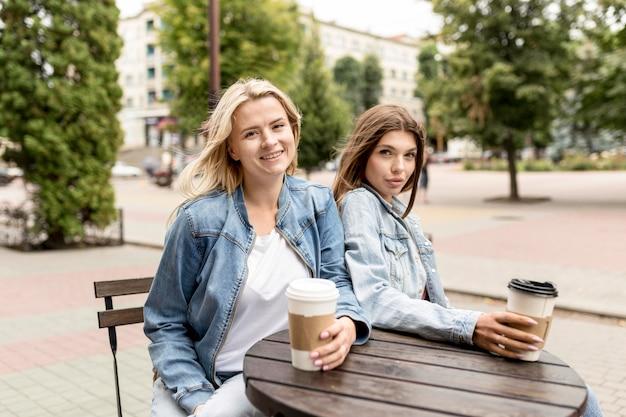 Лучшие друзья наслаждаются чашкой кофе на улице