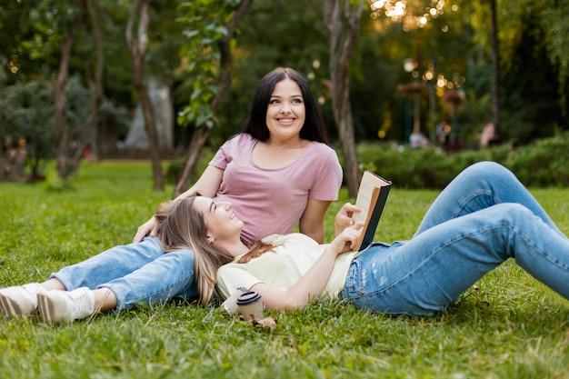 Лучшие друзья наслаждаются своим свободным днем, оставаясь на траве