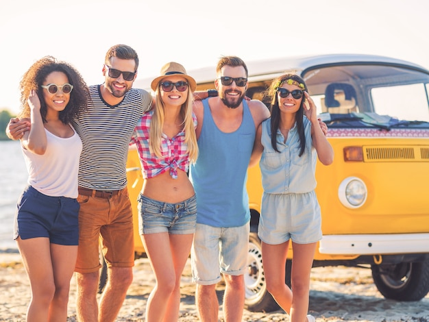 The best friends ever. group of cheerful young people embracing and looking at camera while standing on the beach with retro minivan in the background