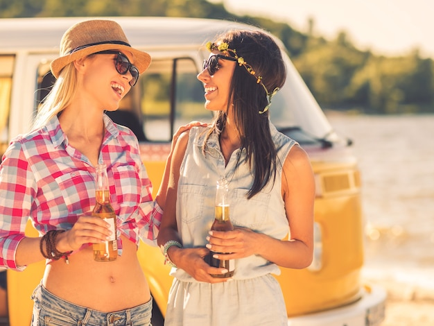 Best friends ever. two cheerful young women holding bottles of beer and looking at each other with smiles while standing near retro mini van