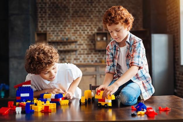 永遠の親友。家で一緒に楽しんで遊んでいる間、2人の友好的な兄弟が彼らの注意を集中する建設セットの愛らしい瞬間。