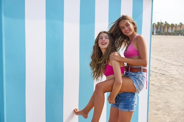 Best friends girls piggyback in summer beach