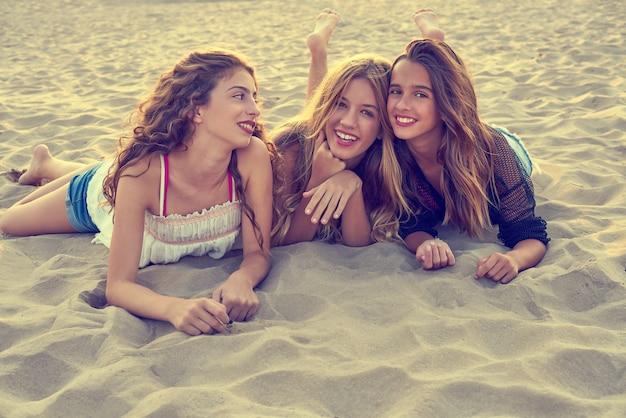 Best friends girls at sunset beach sand