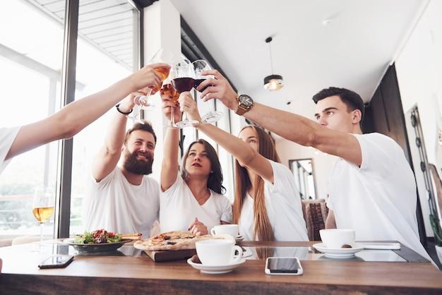 親友は特別な日を祝うために赤ワインのグラスと一緒においしい料理とテーブルで集まりました。