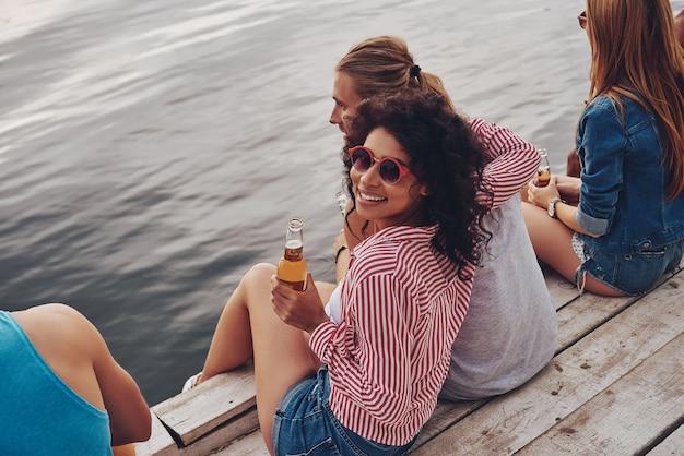 親友。桟橋に座って笑顔でクマを飲むカジュアルな服装で幸せな若者のグループ