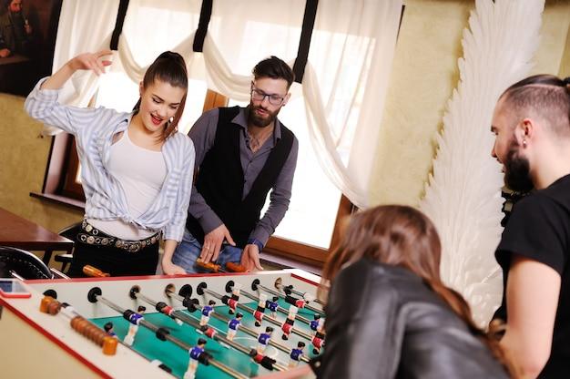 Лучшие друзья - парни и девушки играют в настольный футбол