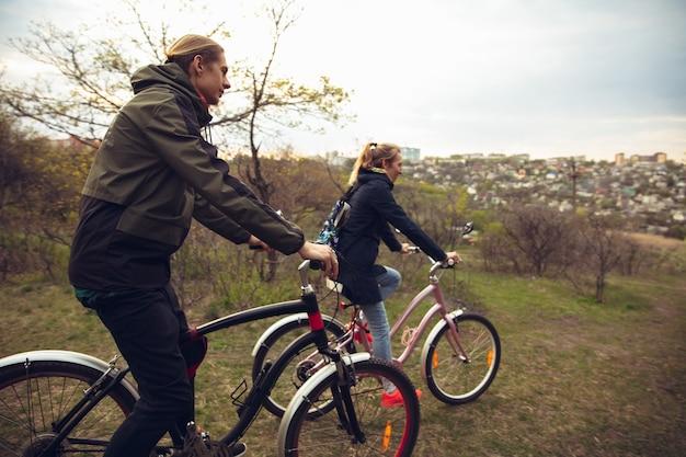 Лучшие друзья веселятся возле загородного парка, катаются на велосипедах, проводят время здоровым. спокойная природа, весенний день, положительные эмоции. спортивный, активный отдых. путешествовать или гулять вместе.