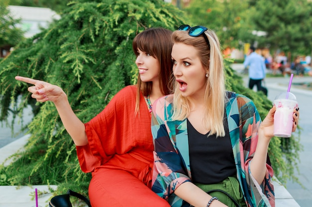 Best friends having fun together and enjoying holidays in sunny modern city