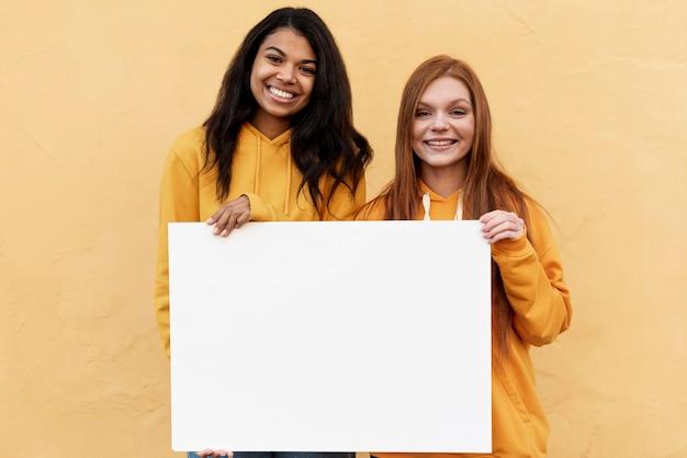 Best friends holding a blank card