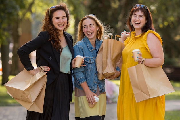 Best friends holding shopping bags outside