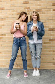 Best friends holding their cups of coffee