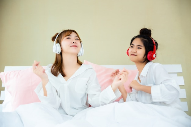 Best friends joyful with listening song in bedroom