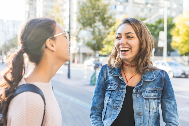 Best friends laughing together in the city