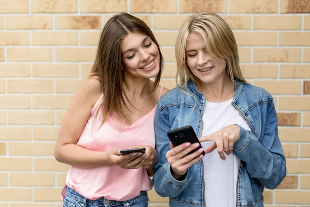 Лучшие друзья смотрят в свои мобильные телефоны на улице
