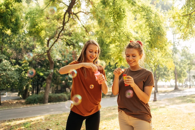 Migliori amici che fanno bolle di sapone all'aperto