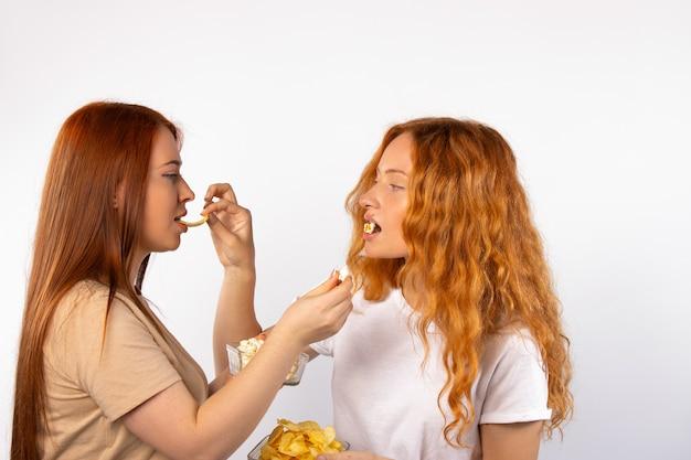 흰 벽에있는 가장 친한 친구가 서로에게 팝콘과 칩을 먹여 맛있는 바삭한 스낵을 제공합니다.