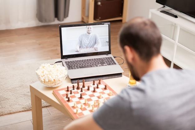 Лучшие друзья играют в шахматы во время видеозвонка во время карантина.