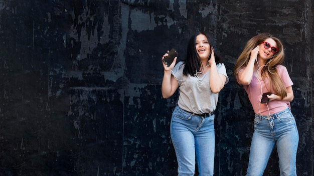 Best friends posing on a dark background with copy space