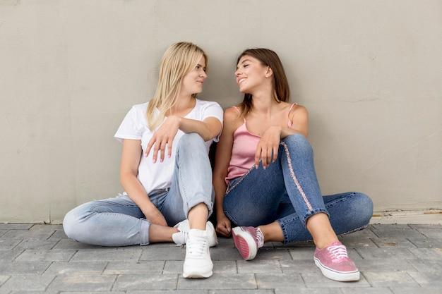 Лучшие друзья позируют на серой стене