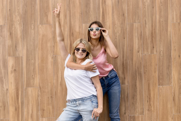 Best friends posing in a silly way on a wooden background