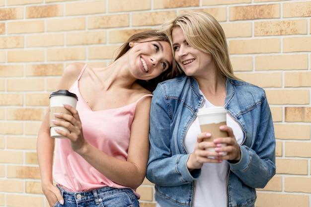 Migliori amici in posa con le loro tazze di caffè